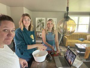 three women preparing food in kitchen